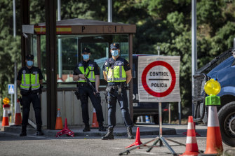 Spanish police officers wait for cars to cross into France at the border checkpoint in El Perthus on Sunday.