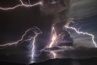 Lightning strikes as a column of ash rises from the crater of the Taal volcano.