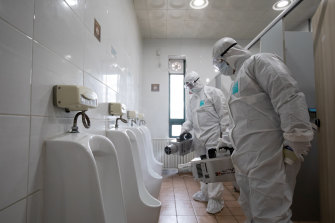 Workers disinfect the toilets at a South Korean bus depot.