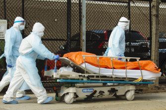 Medical workers in protective clothing move the body of a patient in the Brooklyn borough of New York.