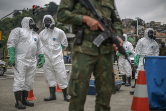 Brazil's Marine Corps soldiers from the Nuclear, Biological, Chemical and Radiological Defence division perform disinfection operations at tram stations under guard in downtown Rio de Janeiro on Thursday.