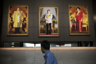 Portraits of the king flanked by his late father, Bhumibol, and his mother, Sirikit, at the Stock Exchange of Thailand in 2019.