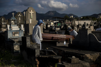 Gravediggers carry the coffin of 89-year-old Irodina Pinto Ribeiro, who died from COVID-19 related complications, at the Inhauma cemetery in Rio de Janeiro in June.