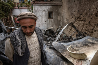 A relative turns away after viewing the destruction of the home destroyed by a US drone, a strike the US now admits only killed innocent civilians.