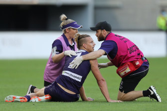 Nat Fyfe of the Dockers receives attention after a heavy knock from Sam Reid.