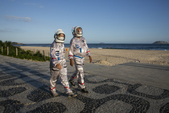 Tercio and Alicea Galdino, dressed in protective astronaut costumes, walk along Ipanema beach in Rio de Janeiro.