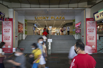 Customers wait in line to enter the Lucky Plaza on Orchard Road in Singapore due to coronavirus restrictions.