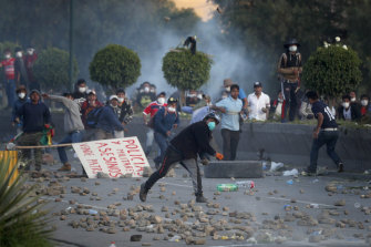 Backers of former president Evo Morales throw stones at police on the outskirts of Cochabamba, Bolivia. Officials now say at least eight people died when Bolivian security forces fired on Morales supporters the day before, in Sacaba.