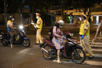 Motorcyclists are stopped at a security checkpoint earlier this month during a stay-at-home order in Vietnam's Ho Chi Minh City.