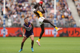 Hawthorn's Changkuoth Jiath takes an athletic overhead mark in front of Fremantle star Michael Walters.