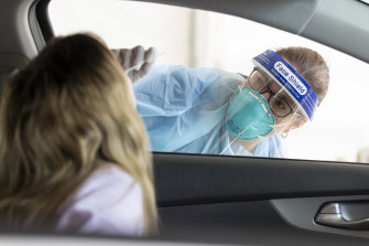 Health officials test a woman for COVID-19 at a drive-through clinic in Mindarie.