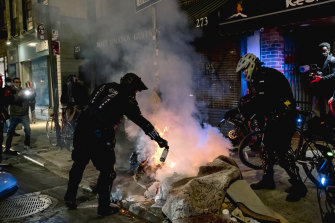 New York City Police officers extinguish a fire at a protest after the election.