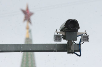 A surveillance camera operates as the Spasskaya tower of the Kremlin stands beyond in Moscow, Russia.