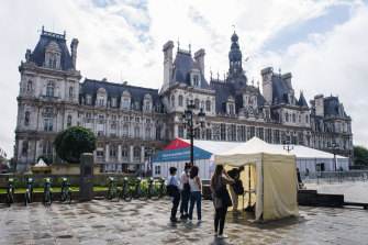 People register for COVID-19 vaccinations at tents outside the Hotel de Ville, the Paris Mayor's office, on Monday.