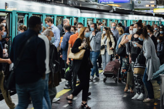 Morning rush hour commuters wear protective face masks while boarding and exiting a train at Saint-Lazare station in Paris this week.