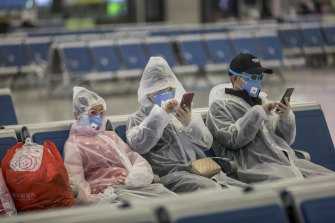 Travellers at a train station in Shanghai wear gear to try to protect themselves from coronavirus.