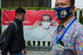 "Pedestrians pass a Jakarta poster showing President Joko Widodo, who has said Indonesia's management of the coronavirus ""has not been bad""."