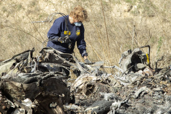 An investigator examines wreckage from the helicopter crash that claimed the lives of Kobe Bryant and his daughter Gianni.