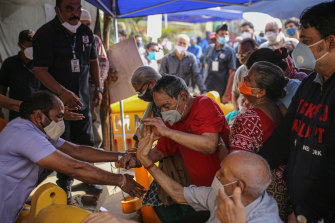 Elderly people struggle in a queue at an entry gate of a Covid-19 vaccination centre in Mumbai.