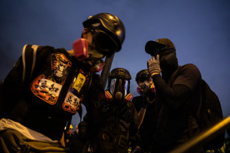 Demonstrators wear gas masks during a strike rally at Tamar Park.