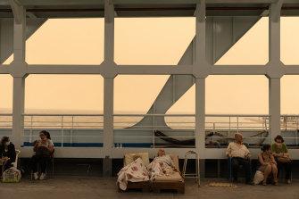 Una pareja de ancianos espera en un ferry utilizado para albergar a residentes y turistas que han evacuado sus hogares.