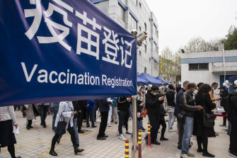 People wait outside a COVID-19 vaccination center for foreign nationals in Shanghai, China.