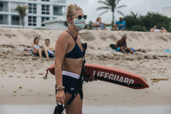 A lifeguard wearing a protective mask stands guard Delray Beach in Florida.