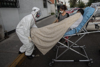 A suspected coronavirus patient is taken to an ambulance in Mexico City on Friday.