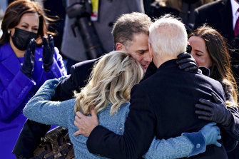 Vice-President Kamala Harris applauds as President Joe Biden is embraced by his son Hunter, First Lady Jill Biden and daughter Ashley: 'We will get through this. Together'.