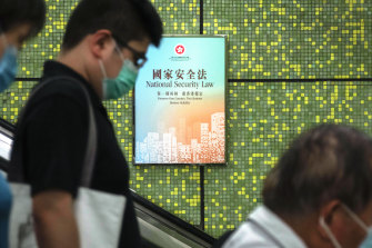 Pedestrians ride an escalator at a train station in Hong Kong where Government National Security Law posters have been plastered on walls.