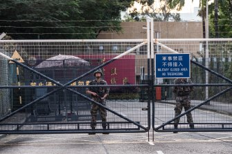 Members of the PLA stand guard at an entrance to their barracks in the Kowloon Tong area of Hong Kong.