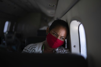 Telma Maria looks out of the window as a doctor monitors her 89-year-old father who is suffering from COVID-19 and is being airlifted to a hospital in Manaus, Brazil.