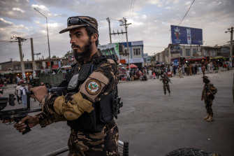 Taliban fighters control their positions near the entrance to the airport in Kabul on Monday.