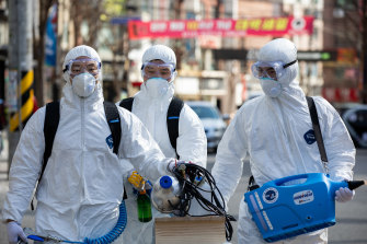 Workers in protective suits disinfect a street in Seoul, South Korea.