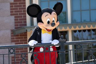 A performer dressed as Mickey Mouse entertains guests during the reopening of the Disneyland theme park in Anaheim. The usual hugs and close selfies with characters are not allowed though.