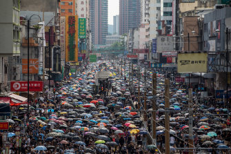 Demonstrators walk on the main street during a protest in the Yuen Long district of the New Territories in Hong Kong, China, on Saturday.