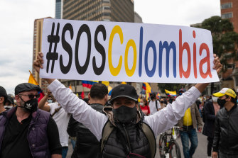A demonstrator holds a banner during a protest against the government's tax reforms in Bogota, Colombia.