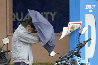 A man holds un umbrella against strong wind and rain on Tuesday in Tokyo.