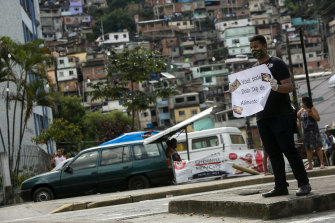 Felipe Feliz, resident of Morro do Borel community, holds a sign that reads in Portuguese 'Can you donate 1kg of food?' during the pandemic in Rio de Janeiro.