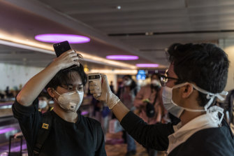 An arriving passenger has his temperature checked at Changi Airport, Singapore.