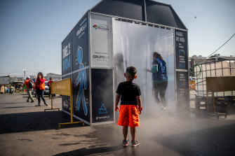 A child watches as people pass through a decontamination chamber at the La Vega Central fruit and vegetable market in Santiago, Chile, in 2020.