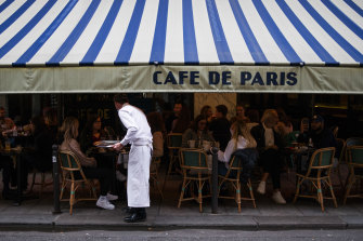 A waiter serves customers eating and drinking on the terrace area outside Cafe de Paris in September, ahead of the enforcement of new COVID-19 restrictions in Paris.