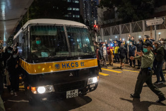 Supporters wave mobile phone lights as a Correctional Services bus leaves court following the sentencing of Joshua Wong, Agnes Chow and Ivan Lam.
