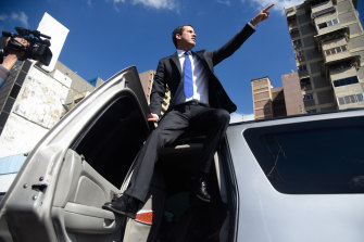 Guaido stands on a car and points to buses arriving with his supporters on board.