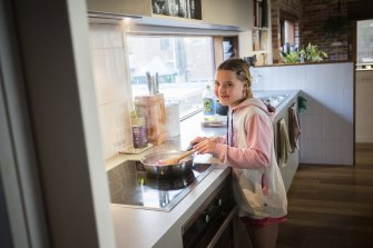 Josie Aberle cooks a meal on an induction cooker. Her parents chose not to connect their house to gas, and also installed a reverse cycle air-conditioner and heat pump hot water.