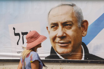 A pedestrian passes an election campaign billboard for Benjamin Netanyahu, Israel's prime minister and the leader of the Likud party, in Tel Aviv, Israel.