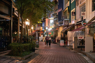 Pedestrians walk along a deserted street in the Boat Quay area of Singapore.
