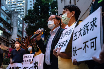 Pro-democracy supporters hold banners and shout slogans outside of the  Western District police station in Hong Kong after at least 14 pro-democracy veterans and supporters were arrested on Saturday.