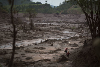 Rescue workers search for victims at the site where the town of Bento Rodrigues stood three days after the Samarco dam burst in 2015.