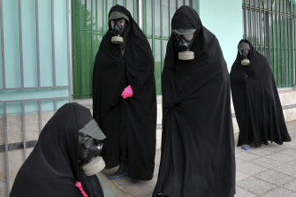 Women wearing protective clothing and chadors arrive at a cemetery in Ghaemshahr, Iran, to prepare the body of a person who died from COVID-19.
